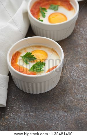 Eggs baked with tomatoes and parsley in the ramekins vertical