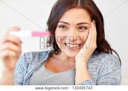 pregnancy, fertility, maternity, emotions and people concept - happy smiling woman looking at pregnancy test at home