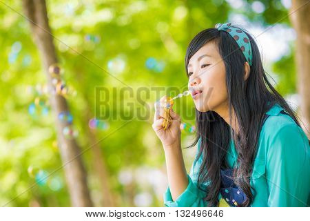Young Asian Female Blowing Bubbles At Green Park Outdoors