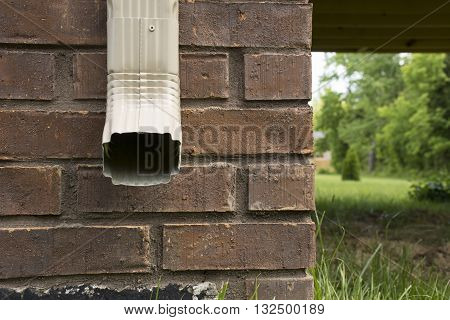 Downspout of a rain gutter against the side of a house facing forward.