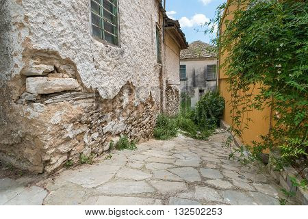 An alleyway of run down houses in an old Greek town.