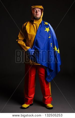 Man dressed as a commercial fisherman wearing traditional protective oilskin waterproof clothing with an EU flag draped over his shoulder.