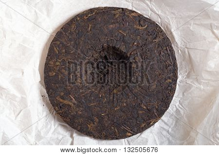 Old pu-erh tea backside on the background of rice paper top view