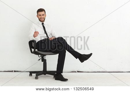 Portrait of handsome young guy sitting in chair against white wall.