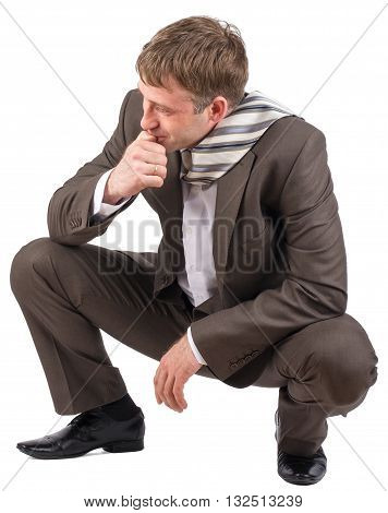 Businessman sitting on his haunches over white background