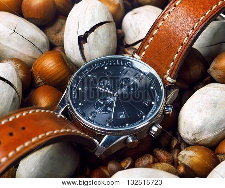 men's watch close up lying flat on the nuts