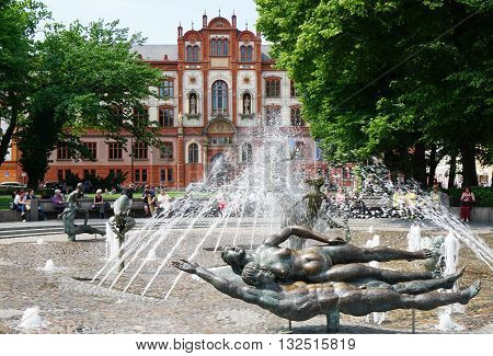 Rostock, Germany - May 30th, 2016: University square with Fountain of Vitality and university building. University of Rostock, founded in 1419, is one of the oldest in northern Europe.
