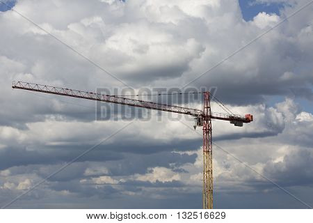 Tower crane. Big crane. Assembling of crane on dramatic cloudy background. Dangerous situation in height. Yellow crane with workman. High construction machinery with load, burden. Hook hangs on rope.