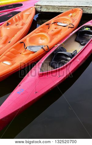 Colored kayaks floating on lake attached to pier in Ottawa Canada closeup
