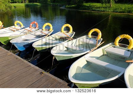 Saint Petersburg, Russia, may 18, 2016: boat dock with moored rowing boats and life ring. Boats at the pier waiting for their captains. Park the boat on the water. A lot of boats on the shore.