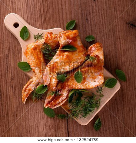 Marinated Chicken Wings On Wooden Board With Herbs