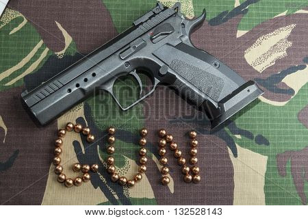 Firearm Pistol Clip And Hand Gun Ammunition on military camouflage background