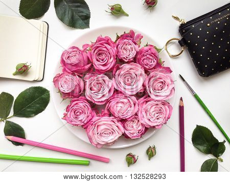 Colorful composition with sketchbook roses and accessories. Flat lay on white table top view