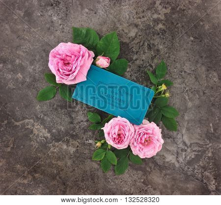 Colorful composition with sketchbook and roses on stone granite background. Flat lay top view
