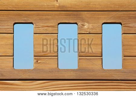 Three windows in a natural wood planks