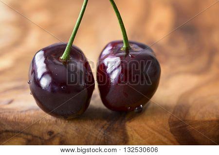 macro two cherries of Vignola on olive wood