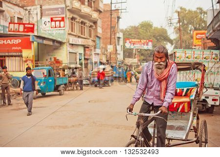 VARANASI, INDIA - JAN 1, 2016: Elderly man with white beard driving by bicycle with cart on street of indian city on January 1, 2016. Varanasi urban agglomeration had a population of 1435113