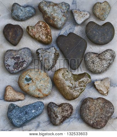 Collection of natural heart rocks on marble stone slab