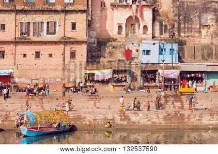 MADHYA PRADESH. INDIA - DEC 27. 2015: People walking near river bank of old indian city with rustic indian houses and riverboats on December 27, 2015 in India. Population of Chitrakoot is 22294 people