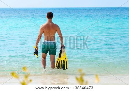 men wearing on yellow mask and flippers going snorkeling in blue ocean