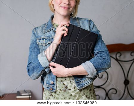 Close up woman holding a tablet in a covering and smiling