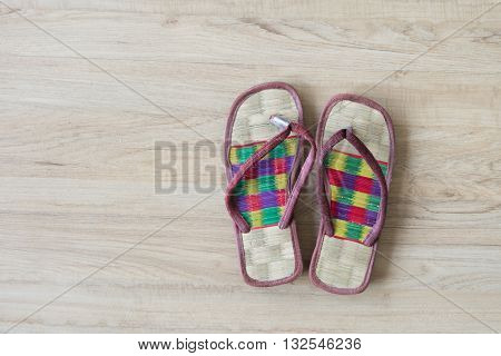 Thai local cozy weave sandal on wooden floor. slipper at home feel comfortable relax. knolling concept. poster