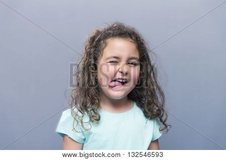 Little Girl Squinting Eyes While Showing Tongue At Camera