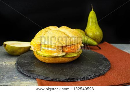 Healthy Vegetarian Veggie Sandwich with French soft cheese pear and honing on black stone plate