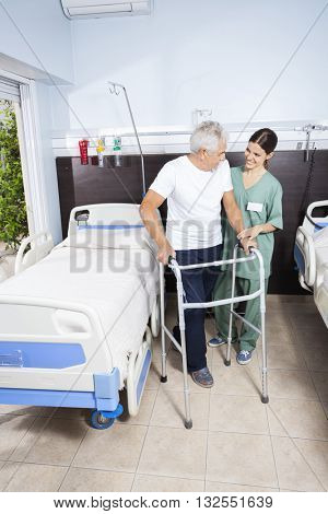 Caretaker Looking At Senior Patient Using Walker