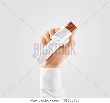 Blank white candy bar plastic wrap opened mockup hold in hand, clipping path. Clear chocolate packaging template. Choco factory branding candybar package mock up. Sweet pastry shop energy bar cover