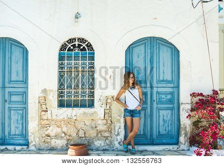 Young blond woman at typical greek traditional town with colorful buildings on Kastelorizo Island, Greece, Europe