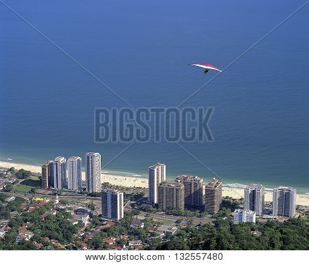 hang glider flying over the Sao Conrado neighborhood after jumping the ramp located in Pedra Bonita