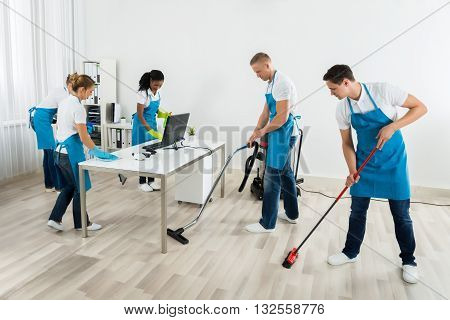 Group Of Male And Female Janitors In Uniform Cleaning The Office