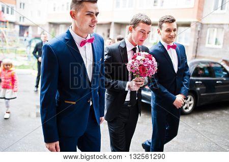 Groom with groomsman background wedding cars outdoor