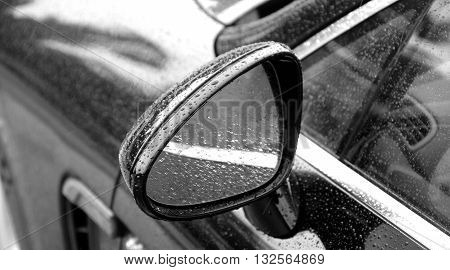 Rain drops on car mirror after water protection repellent coating
