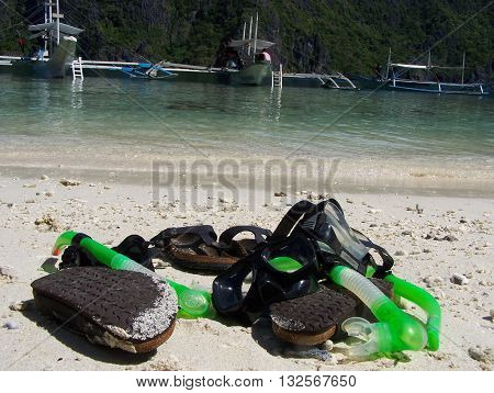 Swimming gear on a tropical beach in the foreground