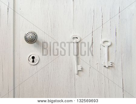 Old cracked gray door with a keyhole decorated with 2 keys: right and wrong keys puzzle. Choice of right decision concern