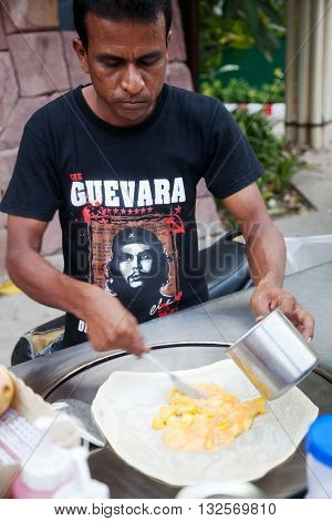PATTAYA / THAILAND - MARCH 22, 2016: Arabic man cooking a crepe stuffed with mango on a street food cart in Thailand wearing Che Guevara T-shirt