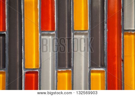 Colorful glass vertical rectangular tiled wall close-up: yellow red white black pattern
