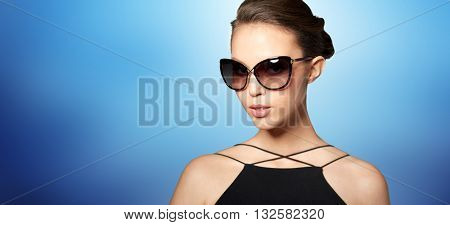 accessories, eyewear, fashion, people and luxury concept - beautiful young woman in elegant black sunglasses over blue background