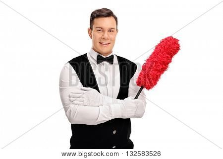 Young cheerful butler holding a duster and looking at the camera isolated on white background