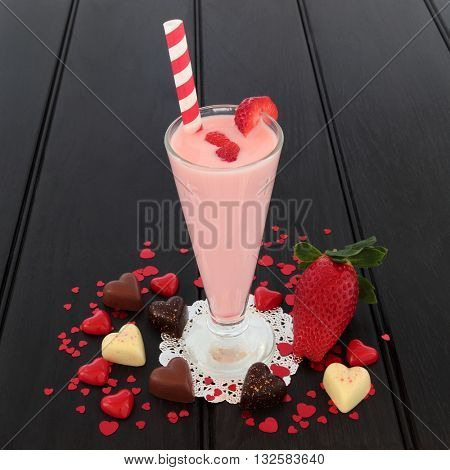 Strawberry smoothie drink with heart shaped chocolates and decorations and fresh fruit over dark wood background. High in vitamins, anthocyanins and antioxidants.