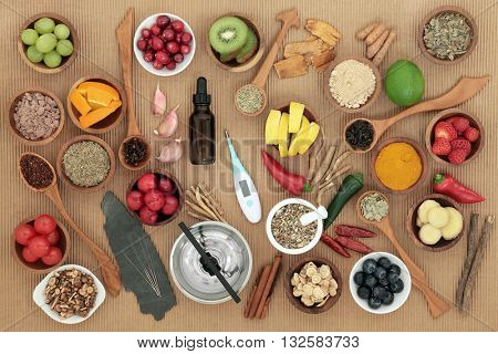 Alternative medicine and food selection for cold remedy with acupuncture needles, moxa sticks and thermometer over ridged brown paper background.