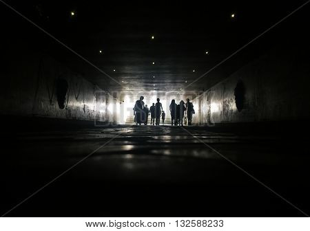 Silhouettes of people walking in pedestrian tunnel