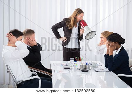 Unhappy Businesswoman Shouting Through Megaphone On Businesspeople In Office