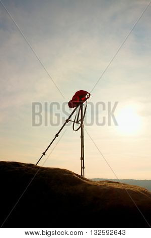 Tripod With Red Baseball Cap On The Peak Ready For Photography. Sharp Autumn Rocky Peaks Increased F