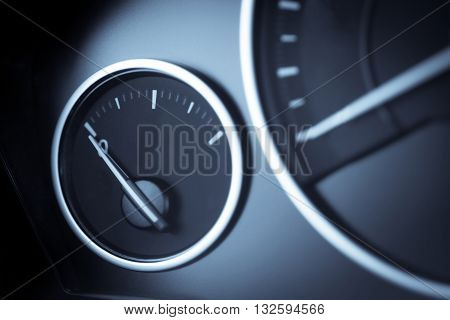 Close-up horizontal shot of a fuel gauge in a car.
