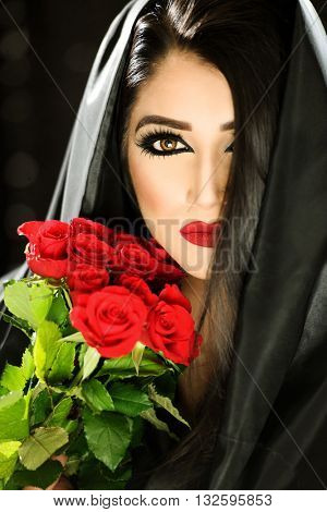 Portrait of a beautiful female model holding red roses and a black veil with red lips
