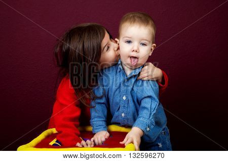 A little girl pulls her younger brother close to kiss him on the cheek. He is drooling with his tongue hanging out.