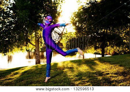 A young girl dressed in a purple butterfly costume leaps in a park as the late afternoon sun streams in behind her.
